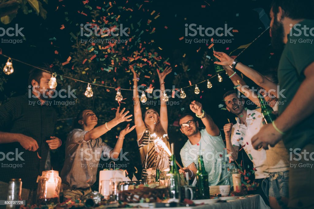 Group of young friends having fun at birthday party stock photo