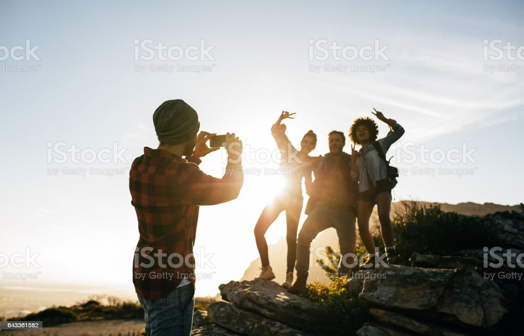 Group of young friends hiking on mountain stock photo