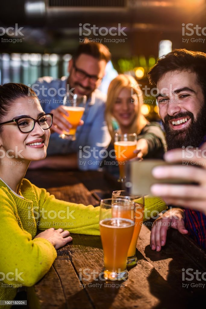 Group of young friends in bar drinking beer toasting, having fun stock photo
