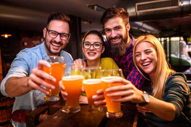 Group of young friends in bar drinking beer toasting the camera Friends in Pub drinking Beer having Fun beer alcohol stock pictures, royalty-free photos & images