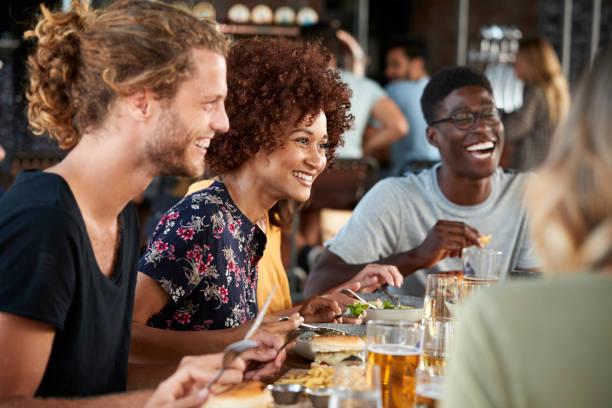 grupo de jóvenes amigos reunión de bebidas y comida en el restaurante - restaurante fotografías e imágenes de stock