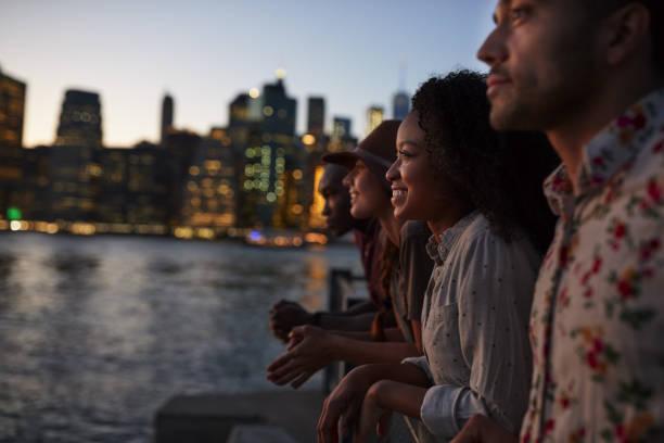 gruppe junger freunde auf reise nach manhattan in der dämmerung - sightseeing in new york stock-fotos und bilder