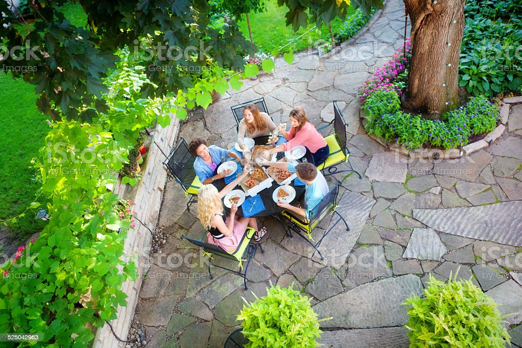 Group of Young Friends Pizza Party in Outdoor Backyard Patio stock photo