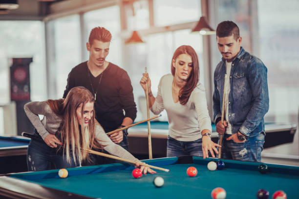 group of young friends playing billiard - pool cue stock photos and pictures