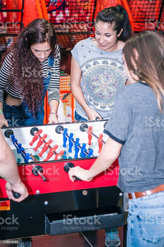 Group of young friends playing foosball stock photo