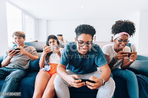 Group of young friends playing mobile games on smartphone