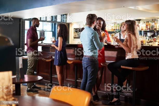 Group of young friends relaxing in bar standing at counter picture id1030952564?b=1&k=6&m=1030952564&s=612x612&h=xmoq6a7o6yxtyhvsike8ndrlztwvbxck4a0nlffwrme=