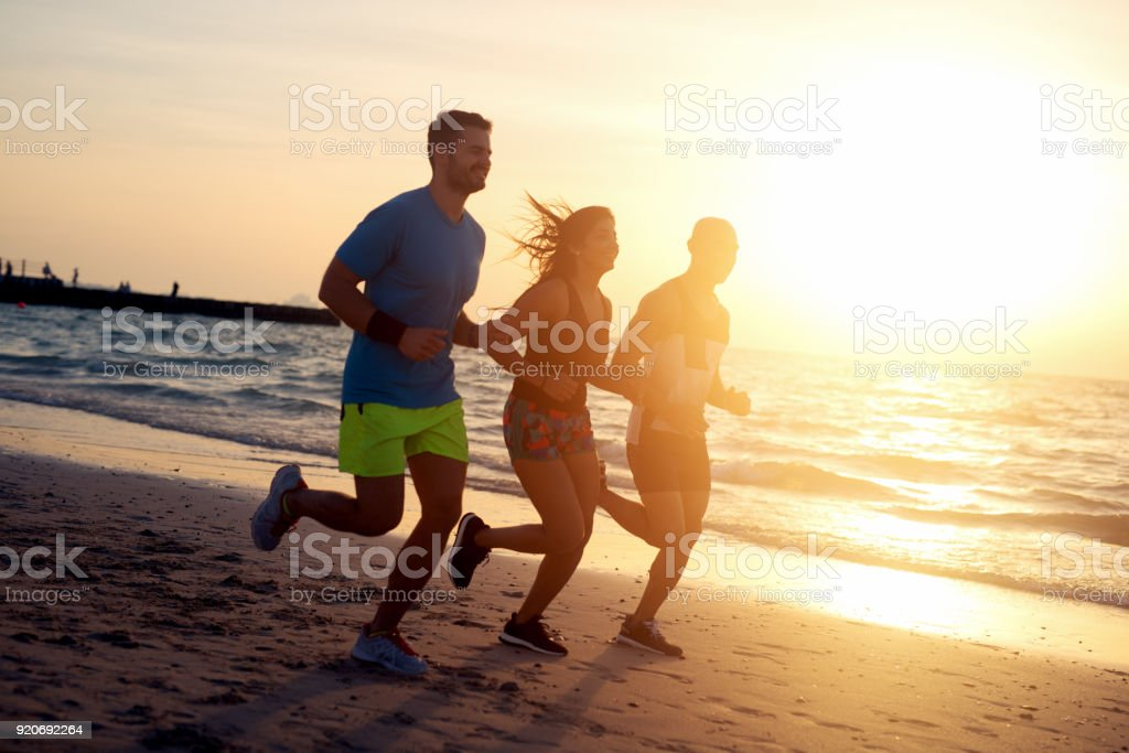 Group of young friends running at the beach on beautiful summer sunset. stock photo