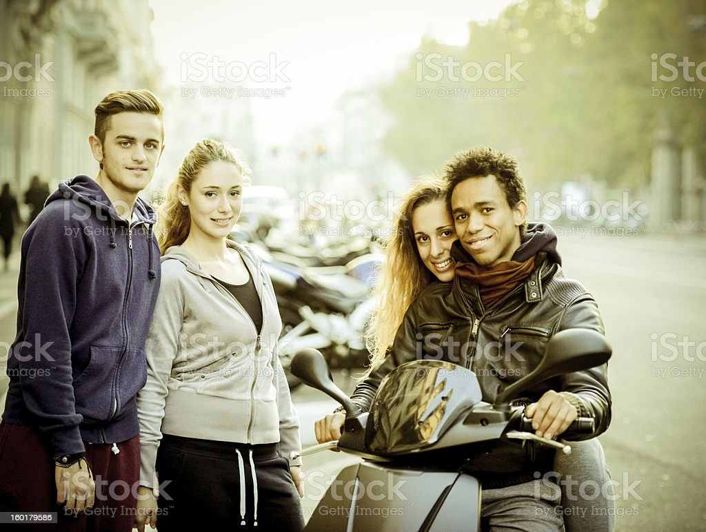 Group of young friends with scooter on the street royalty-free stock photo