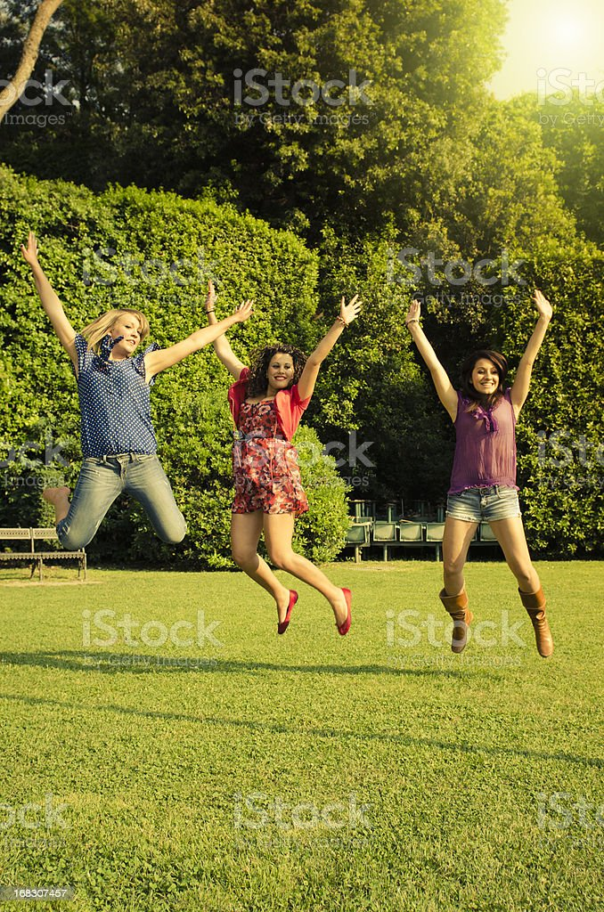 Group of young girl jumping outdoors and having fun royalty-free stock photo