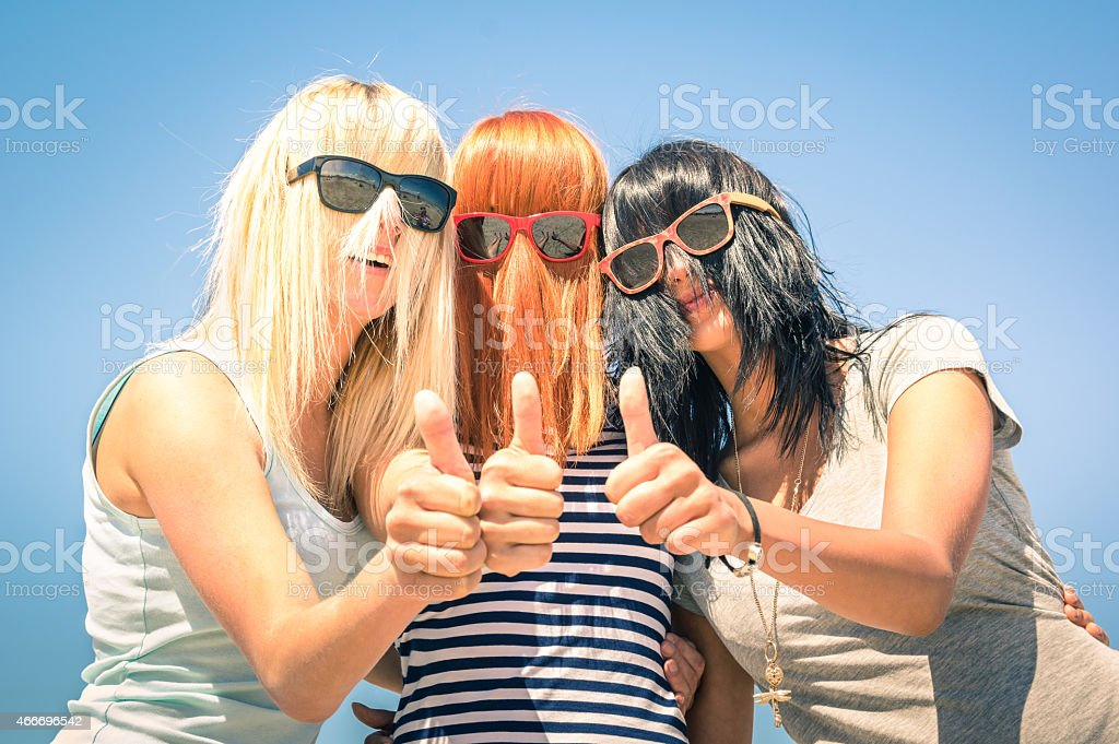 Group of young girlfriends with funny multicolored hairs stock photo