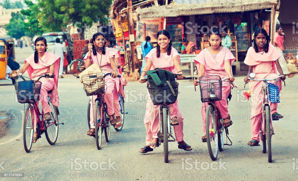 Group of young girls, dressed in school uniform going home on the bicycles. stock photo