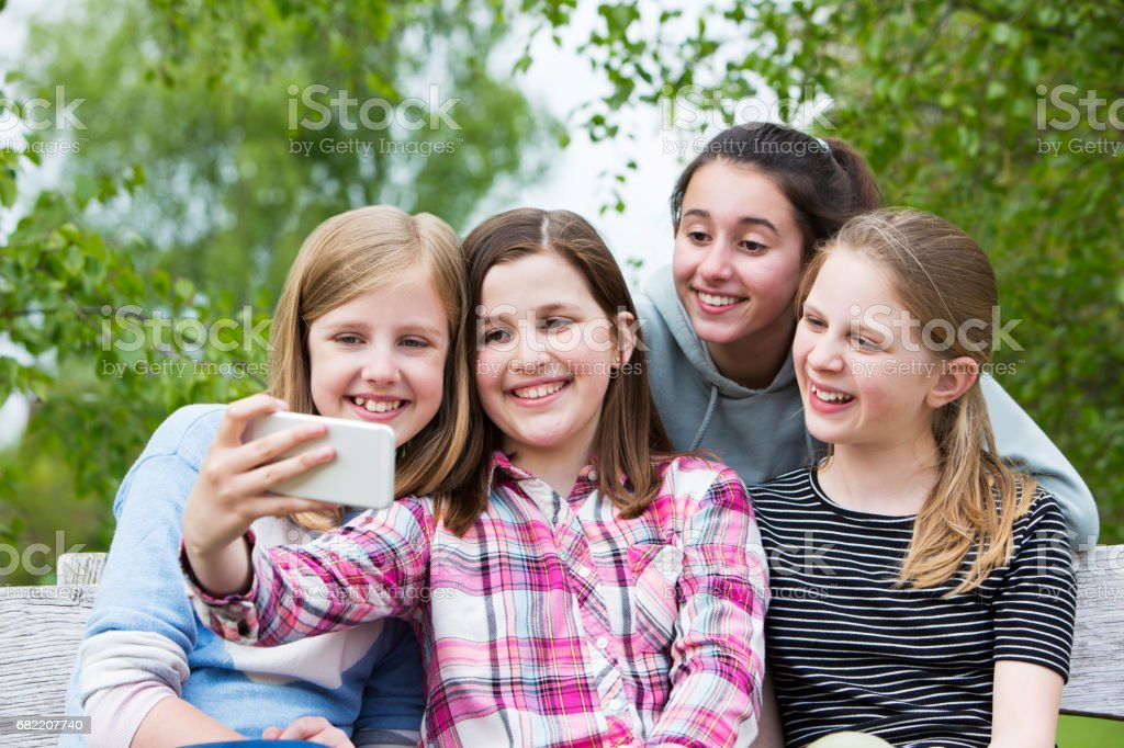 Group Of Young Girls Posing For Selfie In Park stock photo