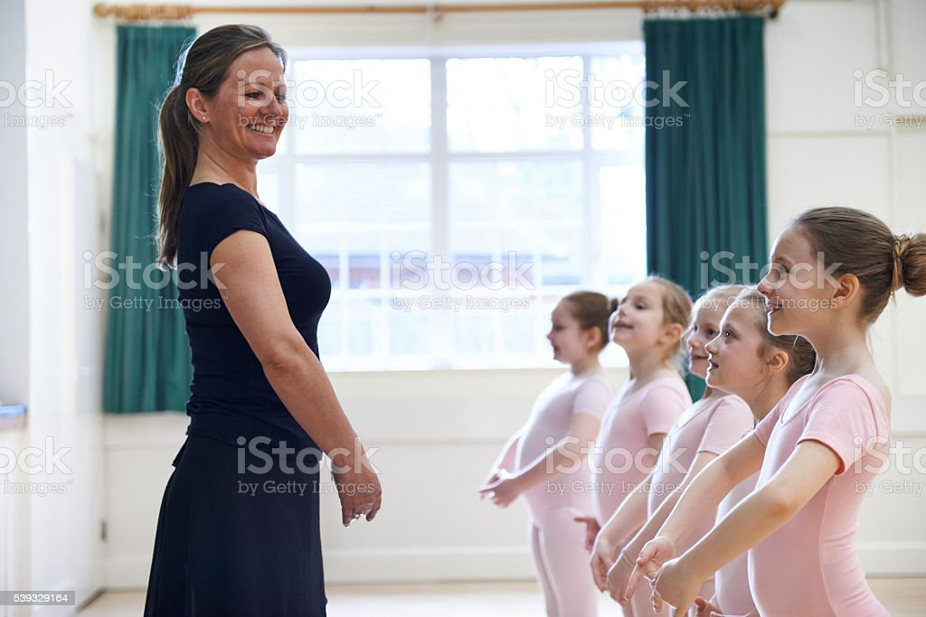 Group Of Young Girls With Teacher In Ballet Dancing Class stock photo