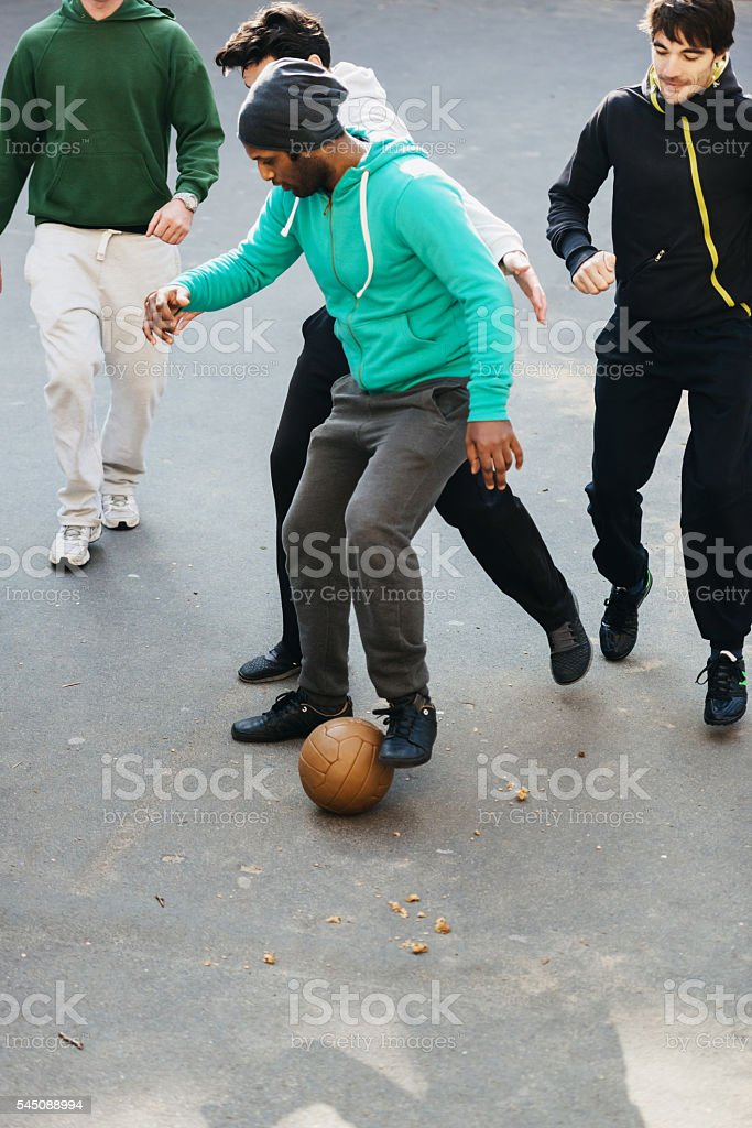 A group of young guys playing soccer on an urban sports ground,...