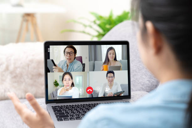 Group of young happy asian work from home meeting or brainstorming online video conference application on 5G internet with covid coronavirus business continuity plan via tablet or notebook computer. stock photo