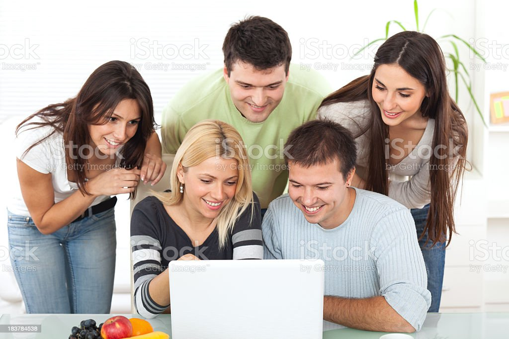 Group of young happy people working on laptop computer royalty-free stock photo