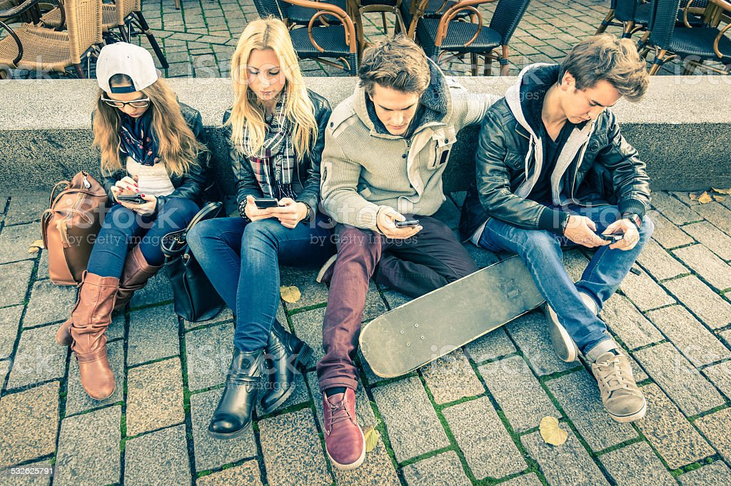 Group of young hipster friends playing with smartphone stock photo