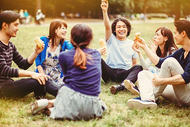gruppe von jungen japanischen personen in the park - mensch isst gras stock-fotos und bilder