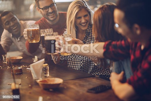 Cheerful friends toasting with beer and having fun in a bar. Focus is on blond woman talking to her friend.