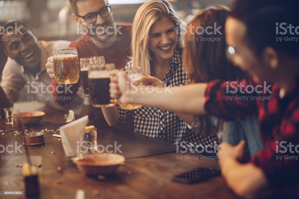 Group of young joyful friends having fun while toasting with beer in a pub. stock photo