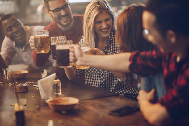 group of young joyful friends having fun while toasting with beer in a pub. - bar zdjęcia i obrazy z banku zdjęć