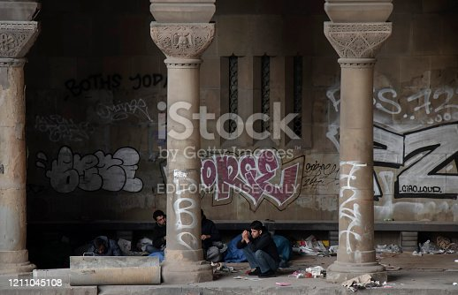 Belgrade, Serbia - October 17, 2019 : Group of young male refugees waking up in a dirty shelter under the city street downtown bridge