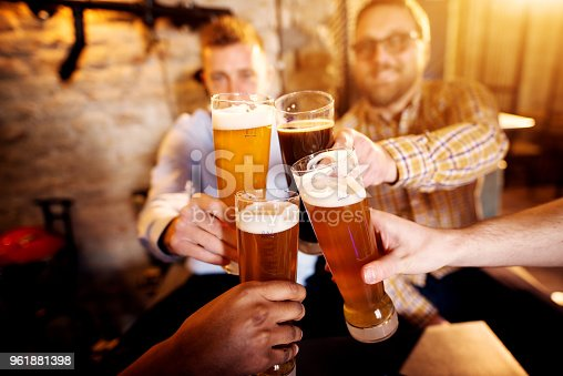 istock A group of young men clinking glasses with a beer in the sunny pub. 961881398