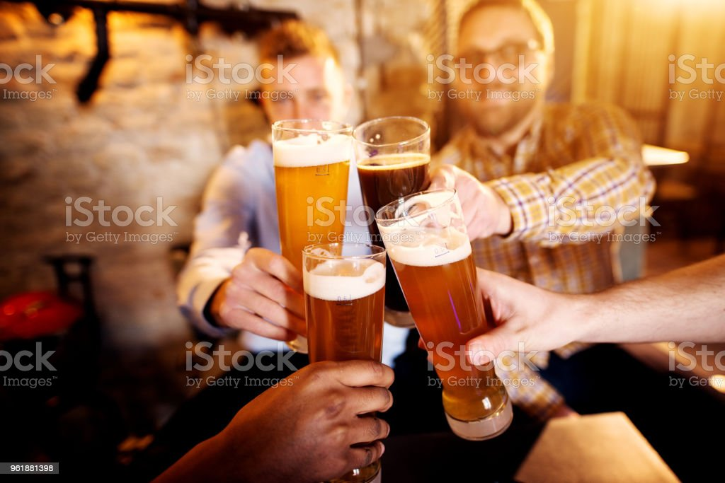 A group of young men clinking glasses with a beer in the sunny pub. stock photo