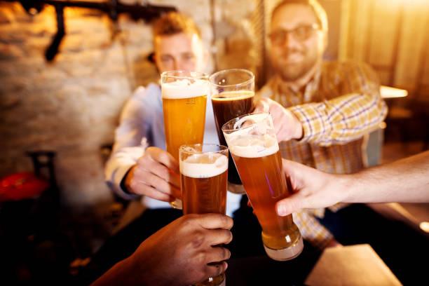 一群年輕男子在陽光明媚的酒吧裡喝著啤酒, 拿著酒杯。 - 啤酒 個照片及圖片檔