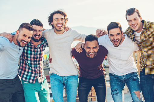Multi-ethnic group of young men holding together and laughing.