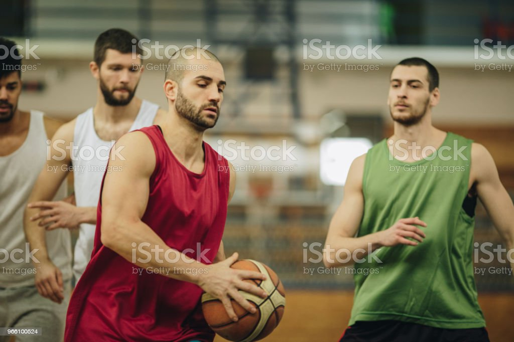Group of young men playing basketball in school gymnasium. - Royalty-free Adult Stock Photo