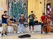 Valencia, Spain - October 9, 2020: Group of young men playing chord instruments in the historic town of the city. Music students sometimes play in the street not only to receive tips for their performance but also to have a chance to practice