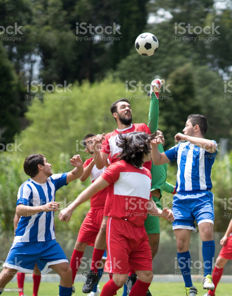 Group of young men playing soccer outdoors stock photo