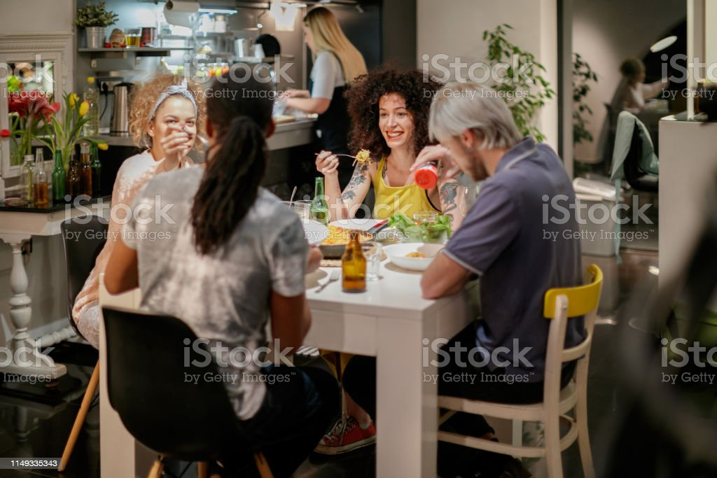 Group of smiling millennial roommates dining at home