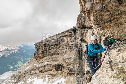 istock group of young mountain climbers on a steep Via Ferrata with a grandiose view of the Italian Dolomites 1050588824