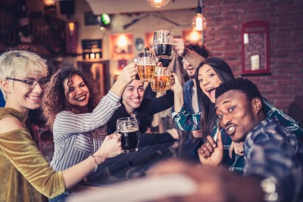 Group of young, multi racial people having fun in a local pub stock photo