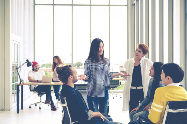 group of young multiethnic creative team engaged brainstorm in small meeting while standing, sitting and talking together in modern office. casual business with teamwork community discussion concept. - cultures stock pictures, royalty-free photos & images