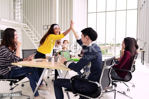 istock group of young multiethnic diverse people gesture hand high five, laughing and smiling together in brainstorm meeting at office. Casual business with startup teamwork community discussion concept. 1031248392