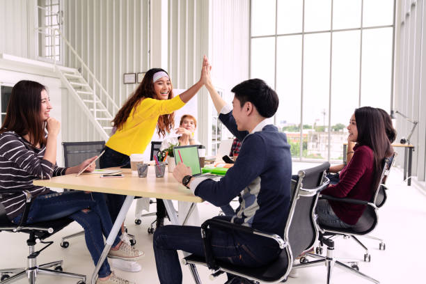 group of young multiethnic diverse people gesture hand high five, laughing and smiling together in brainstorm meeting at office. casual business with startup teamwork community discussion concept. - employee engagement stock photos and pictures