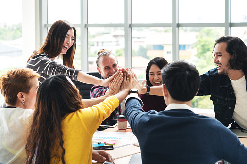 istock group of young multiethnic diverse people gesture hand high five, laughing and smiling together in brainstorm meeting at office. Casual business with startup teamwork community celebration concept. 1031261250