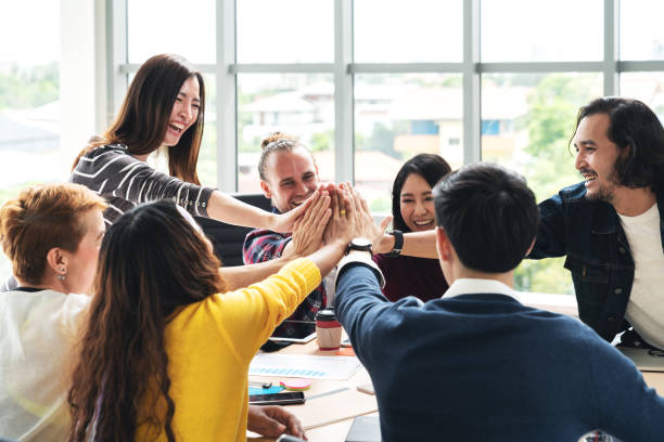 group of young multiethnic diverse people gesture hand high five, laughing and smiling together in brainstorm meeting at office. casual business with startup teamwork community celebration concept. - cultures stock pictures, royalty-free photos & images