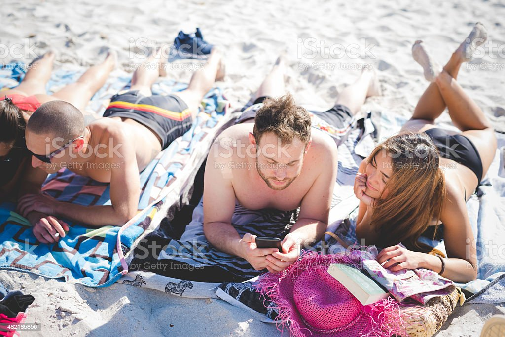 group of young multiethnic friends beach summer stock photo