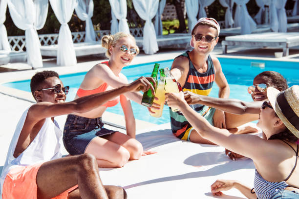 group of young multiethnic friends clinking with beverages at poolside at resort - competition group stock photos and pictures