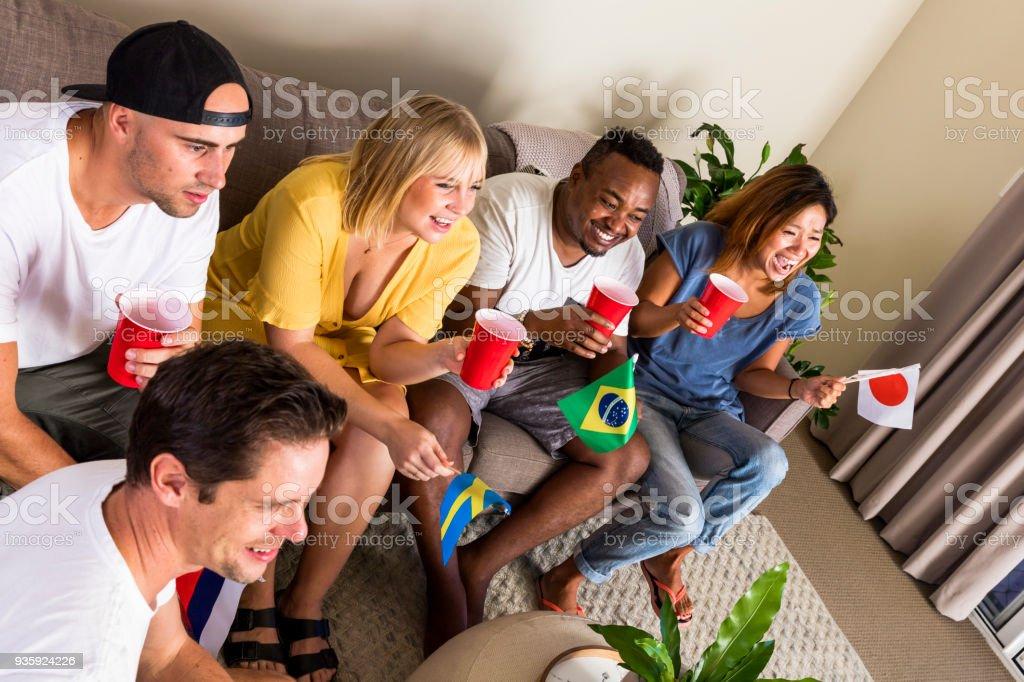 Grupo de jovens multinacional esportes fãs torcendo e assistindo TV - foto de acervo