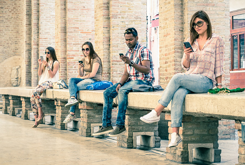 Group of young multiracial friends using smartphone mobile phone