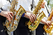 A group of young musicians in the youth brass band play on the golden saxophones at a concert in the city park.