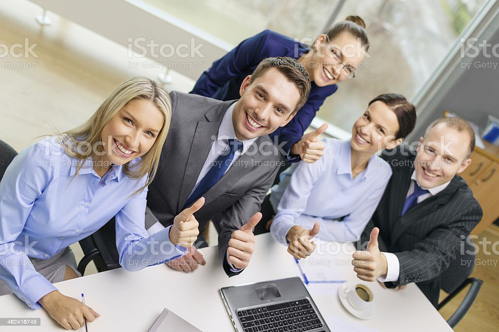 A group of young office workers giving thumbs up business, success, technology and people concept - smiling business team with laptop computer, papers and coffee showing thumbs up in office Achievement Stock Photo
