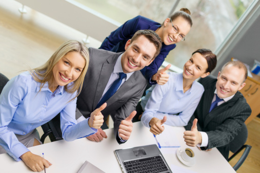 A Group Of Young Office Workers Giving Thumbs Up Stock Photo - Download Image Now