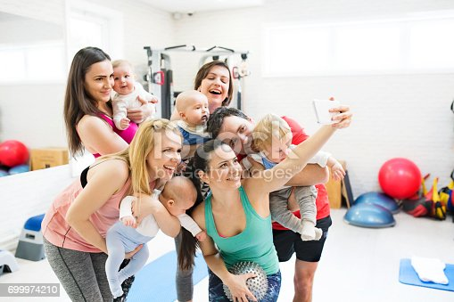 istock Group of young parents and babies in modern gym with personal trainer taking selfie with smart phone. Healthy lifestyle. 699974210